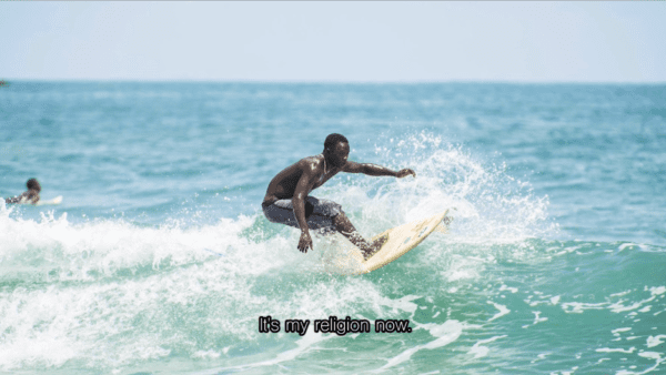 """African surfer catches a wave with the caption """"it is my religion now."""""""