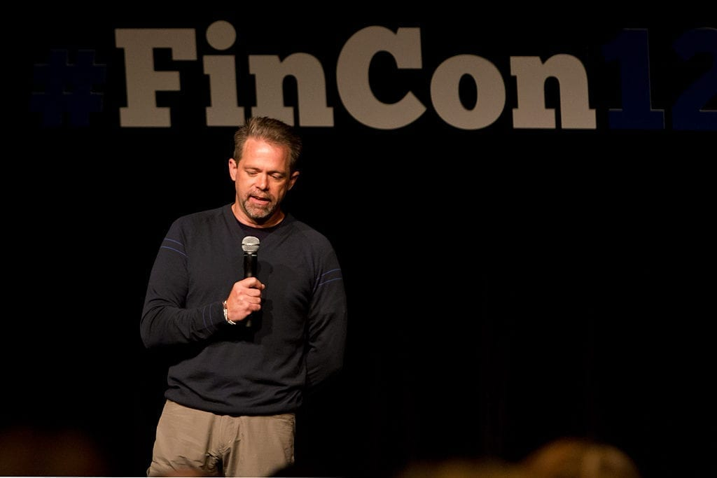 J.D. Roth talking to the FINCON crowd before the opening keynote man speaking at a conference on stage with microphone