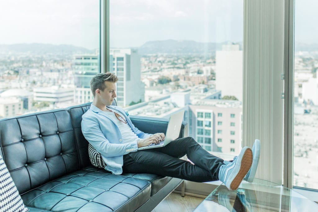 young man with blue vans sneakers sits on couch in los angeles apartment with a laptop entrepreneur