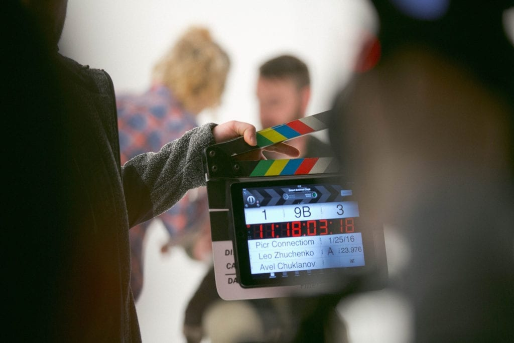 man holds digital film clapperboard slate on a film set with crew