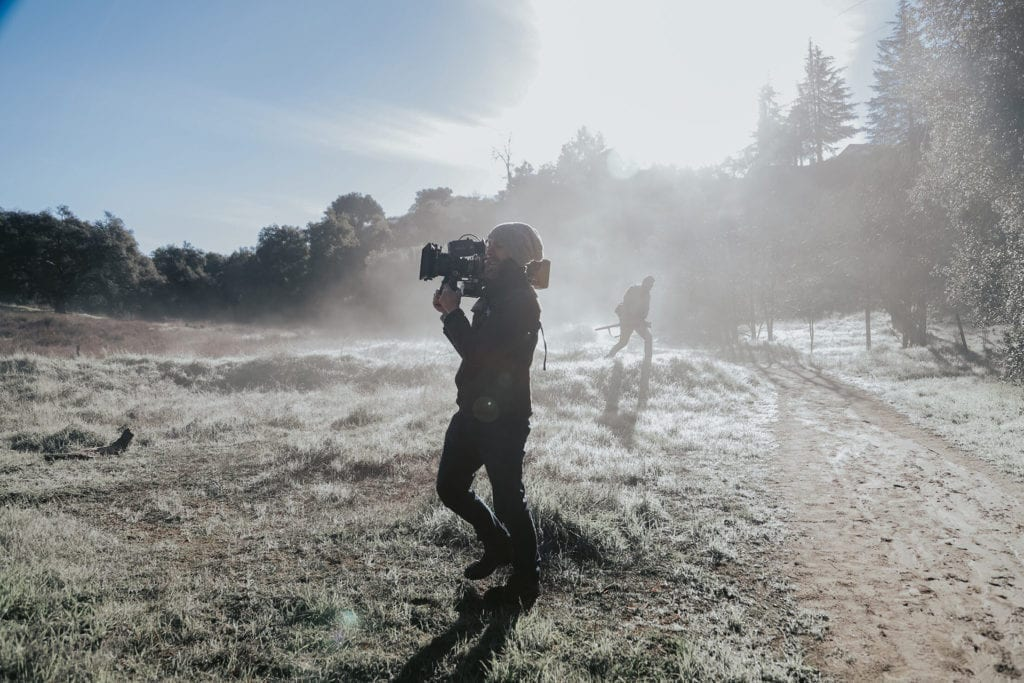 man with camera films in the wilderness outside