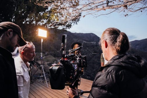 director and cinematographer view camera monitor on independent film set with lighting and sound recording equipment