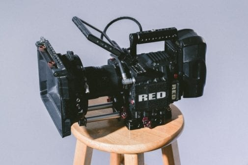 red camera sitting on wooden stool